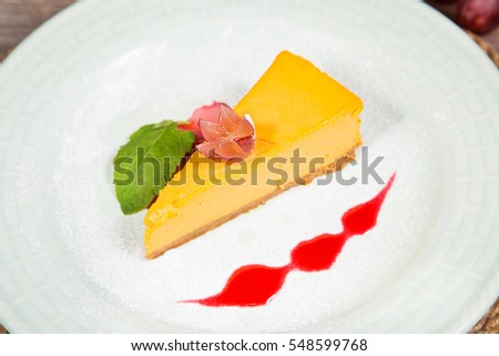 fresh orange cheesecake with grape and mint on plate