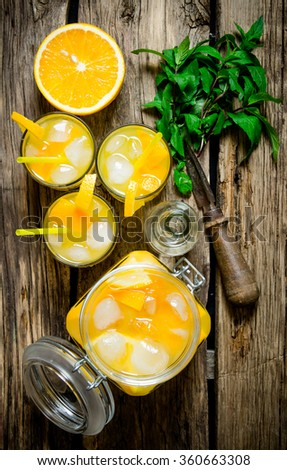 Fresh orange cocktail screwdriver . Orange cocktail with vodka, ice and mint leaves on a wooden table Top view - stock photo
