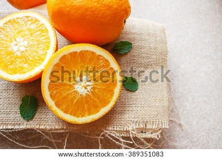 Fresh orange fruit and peppermint on sackcloth