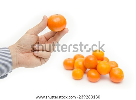 Fresh orange fruit being held with three fingers by a business hand with a pile next to it on a white background suggesting vitamin filled exotic fruits - stock photo