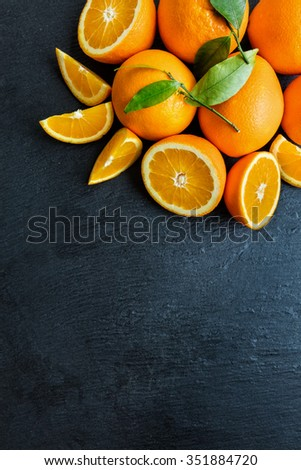 Fresh orange fruit placed on black stone. Shot from aerial view - stock photo