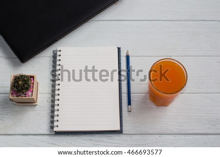 Fresh orange juice and blank notebook on wooden table background selective focus / copy space