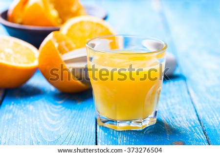 Fresh orange juice and oranges on blue wooden board - stock photo