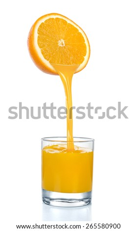 Fresh orange juice flowing from cut orange into the glass. Isolated on a white background. - stock photo
