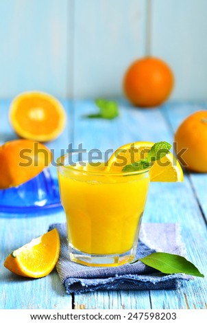 Fresh orange juice in a glass on a blue wooden table.