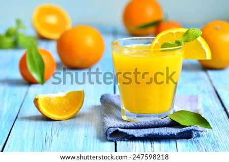 Fresh orange juice in a glass on a blue wooden table. - stock photo