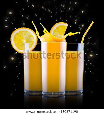 Fresh orange juice in glass with splash isolated on a black background - stock photo