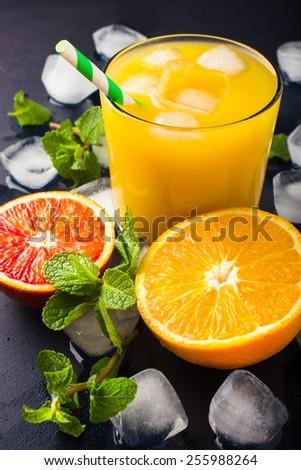 Fresh orange juice,  mint and ice on dark background - stock photo