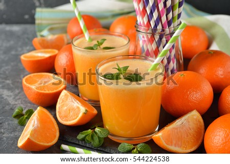 Fresh orange juice on a gray background