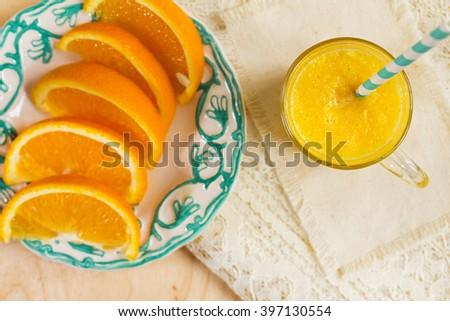 Fresh orange juice. Orange smoothies and sliced orange on the plate. Fresh orange smoothie, downward view on slate. Focus on the glass of juice. - stock photo