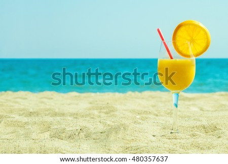 Fresh orange juice with blue sky and sea background, summer concept