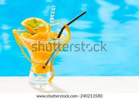 Fresh orange Mojito cocktail  with twist by the swimming pool - stock photo