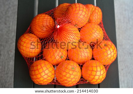 Fresh orange oranges in plastic netting In Market. Food background texture - stock photo
