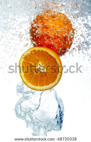 Fresh oranges dropped into water - stock photo