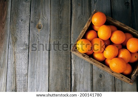 Fresh oranges in an old wooden box. On a wooden background. - stock photo