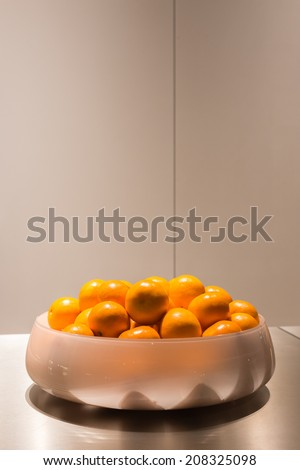 Fresh Oranges in White Glass Bowl on Stainless Steel Table - stock photo
