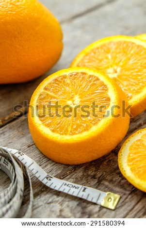 Fresh oranges sliced with measuring tape on wooden ,top view ,still life of fruit, Healthy lifestyle concept - stock photo