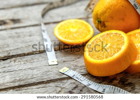 Fresh oranges sliced with measuring tape on wooden ,top view ,still life of fruit , Healthy lifestyle concept - stock photo