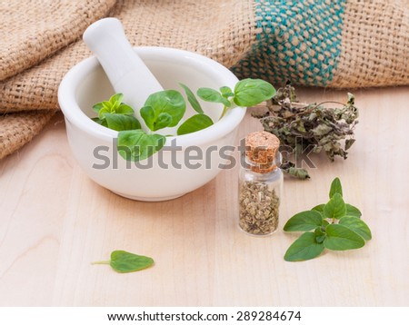 Fresh oregano and dry with mortar on a wooden background. - stock photo