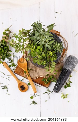 Fresh oregano and sage in mortar over white wooden background. Top view - stock photo