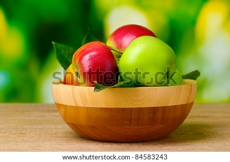 Fresh organic apples in plate on wooden table outside