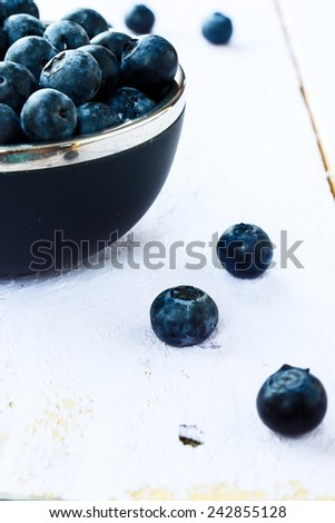 Fresh organic blueberries on white wooden background. Selective focus. Concept for healthy eating and nutrition. - stock photo