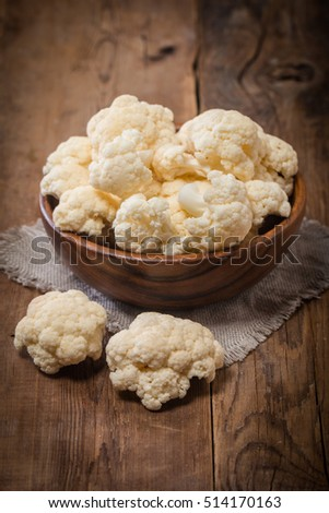 Fresh organic cauliflower in a bowl on wooden background