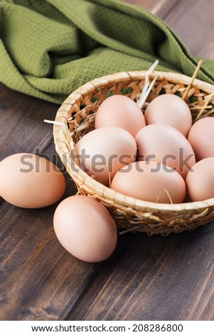 Fresh organic eggs in wooden bowl on dark background. Selective focus. Bio/eco/organic/natural products. - stock photo