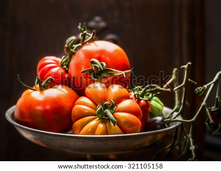 Fresh organic farm tomatoes in steel bowl over dark wooden background, close up - stock photo