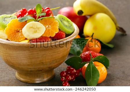 Fresh organic fruit salad (kiwi, strawberry, banana, currant, apple) - stock photo