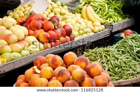 Fresh Organic Fruits and Vegetables At A Street Market Peaches, Nectarine, Pears, Banana, Green Pepper, Peas, and Green Beans - stock photo