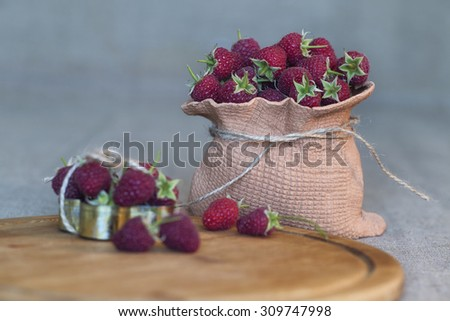 Fresh organic fruits - raspberries against the background of a tree in a small basket made of wood. - stock photo