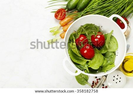 fresh organic garden vegetables in colander bowl on white rustic stone background, healthy cooking concept - stock photo