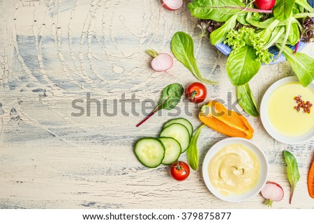 Fresh organic green salad preparation with oil and  dressing ingredients on light rustic background, top view, place for text. Healthy lifestyle or detox diet food concept