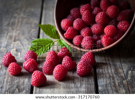 Fresh organic healthy raspberry with mint leaves in clay dish on vintage wooden table background. Rustic style and natural light. Dark food photo. - stock photo