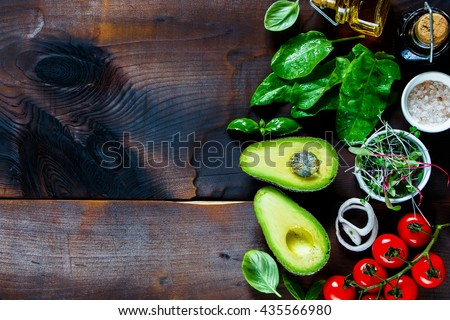 Fresh organic ingredients for salad making: avocado, spinach, tomatoes, sprouts, basil, olive oil on rustic background, top view. Flat lay with place for text. Vegan and healthy food concept - stock photo