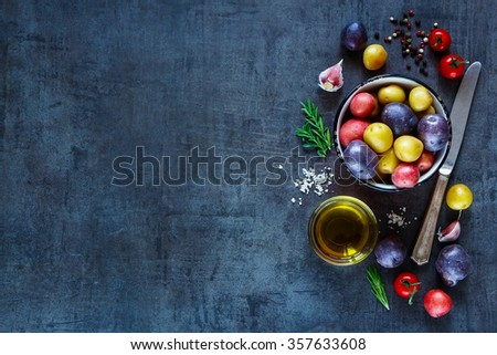 Fresh organic ingredients (potatoes, tomatoes, garlic and olive oil) over dark grunge background with space for text. Top view. Raw vegetables from garden for healthy cooking. - stock photo