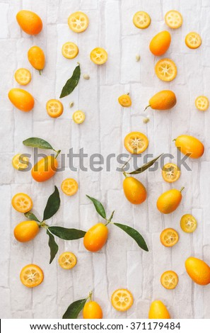 Fresh organic kumquats. Kumquats whole and sliced, still life pattern background, overhead view - stock photo