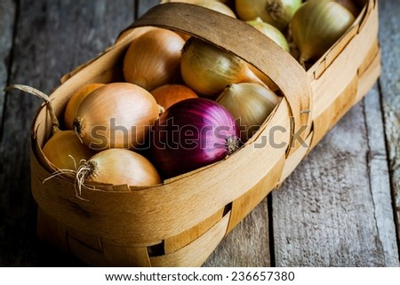 Fresh organic onions in a basket on a wooden background - stock photo