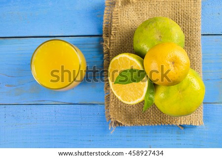 Fresh organic orange and juice on rustic wooden kitchen table in vivid colour and blue background - stock photo