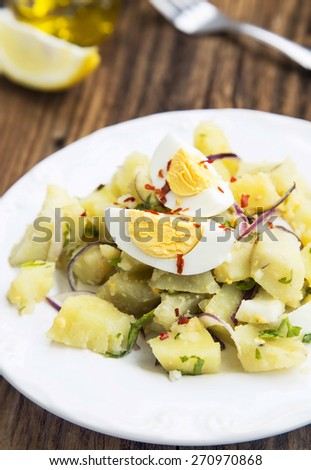 Fresh Organic Potato Salad with Boiled Eggs, Red Onion and Chili Flakes - stock photo