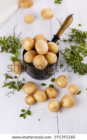 Fresh organic potatoes and thyme in a rustic vintage metal pot on a white wooden background. Top view. Selective focus - stock photo
