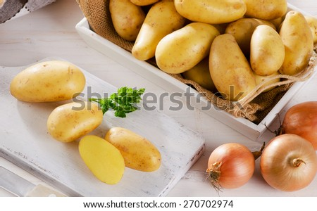 Fresh organic potatoes on a white wooden cutting board. - stock photo