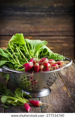 fresh organic radish in colander on old wooden  background, selective focus