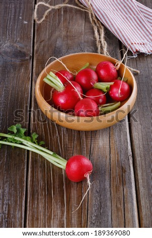 Fresh organic radish on a wooden bowl on a rustic wooden background