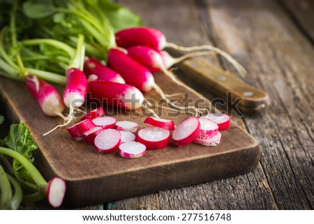 fresh organic radish on wooden cutting board - stock photo