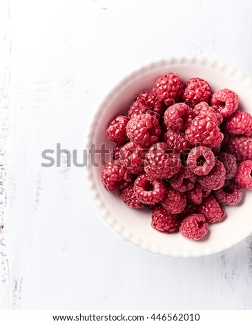 Fresh organic raspberries in a bowl - stock photo