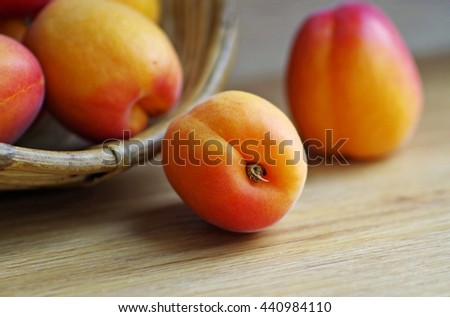Fresh organic ripe apricots in wooden basket on a rustic wooden background. - stock photo