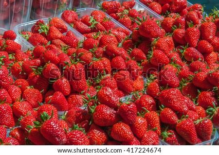 Fresh organic ripe fresh juicy strawberries in plastic boxes background closeup - stock photo