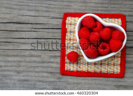 Fresh organic ripe raspberry in a white heart shaped bowl on old wooden background. Selective focus.Healthy food or diet concept. - stock photo